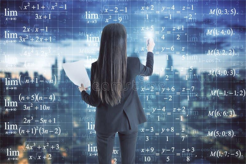Geschäftsfrau, die Formeln betrachtet lizenzfreie stockfotografie