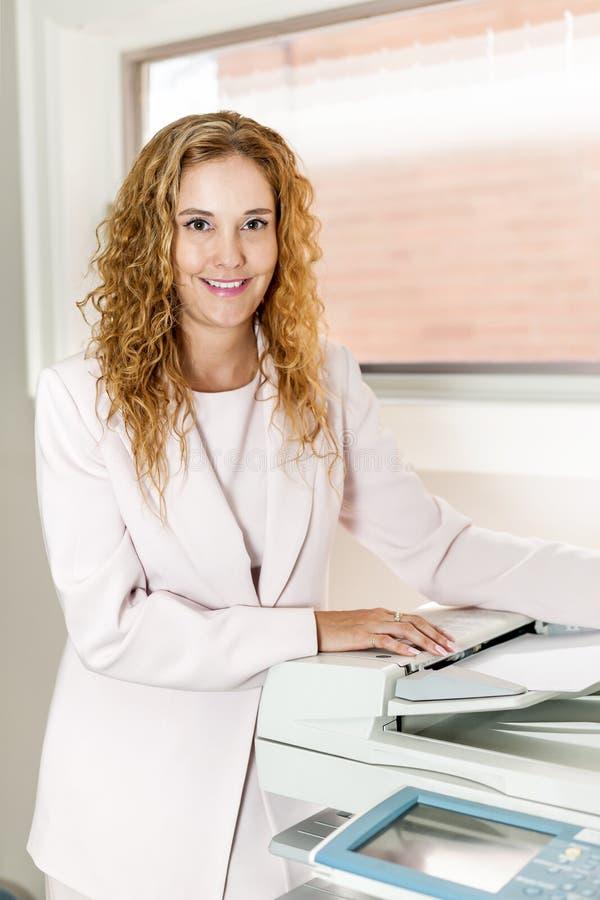 Geschäftsfrau, die Fotokopierer im Büro verwendet stockfoto