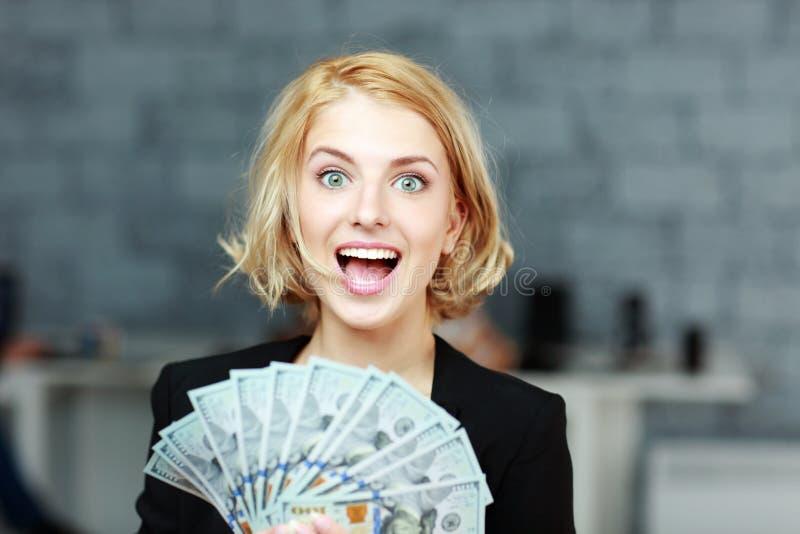 Geschäftsfrau, die Geld mit Freude hält lizenzfreies stockfoto