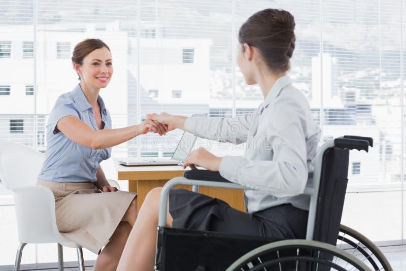 Geschäftsfrau, die Hände mit behindertem Kollegen rüttelt lizenzfreie stockfotos