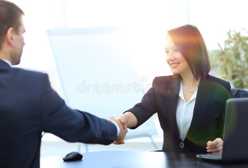 Geschäftsfrau, die Hände mit einem Teilhaber über einem Schreibtisch rüttelt stockfoto
