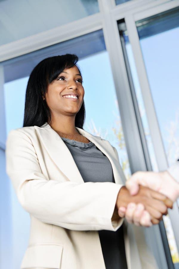 Geschäftsfrau, die Hände rüttelt stockbild