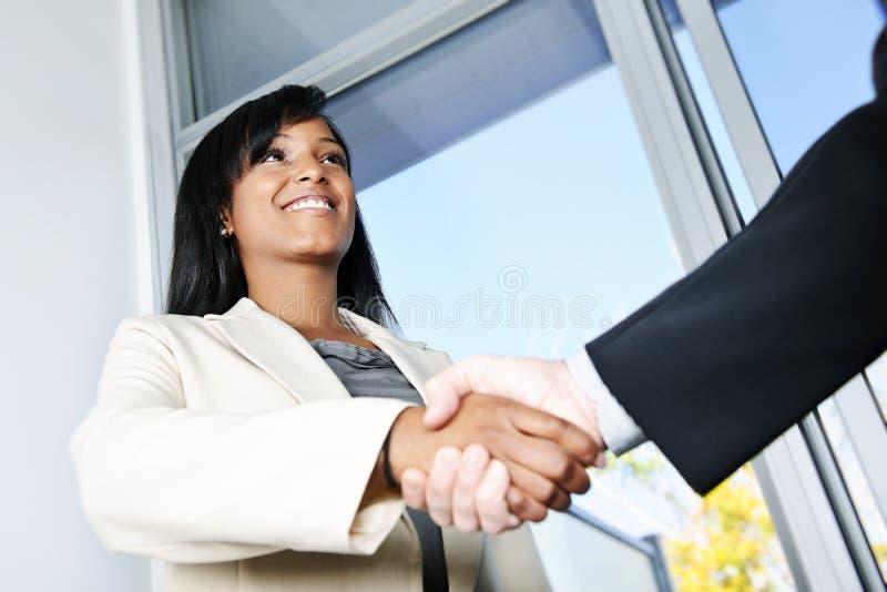 Geschäftsfrau, die Hände rüttelt lizenzfreie stockfotografie