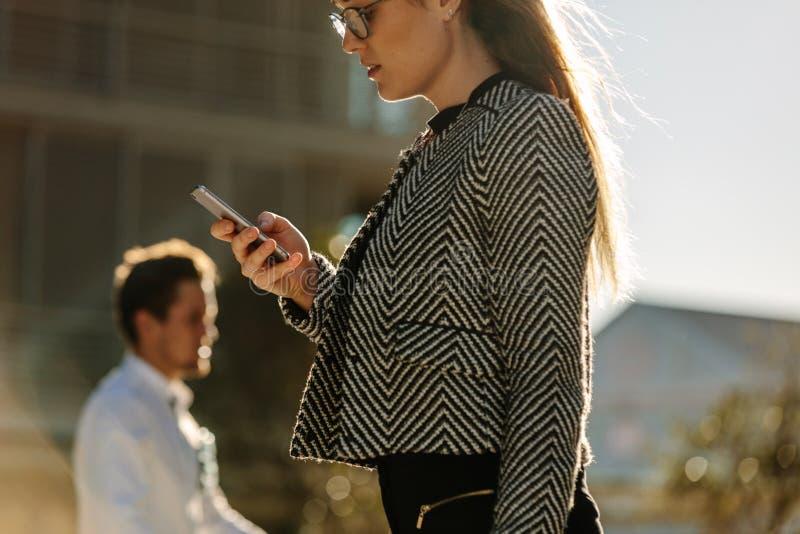 Geschäftsfrau, die Handy beim Gehen auf Straße zum offi verwendet stockfoto