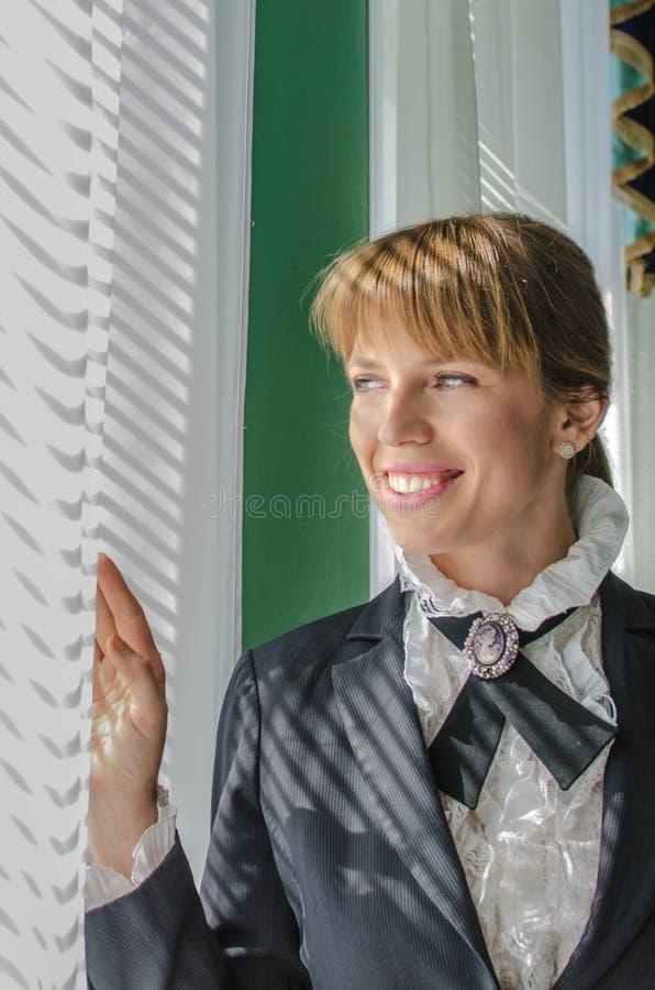 Geschäftsfrau, die heraus das Fenster und das Lächeln schaut lizenzfreies stockbild