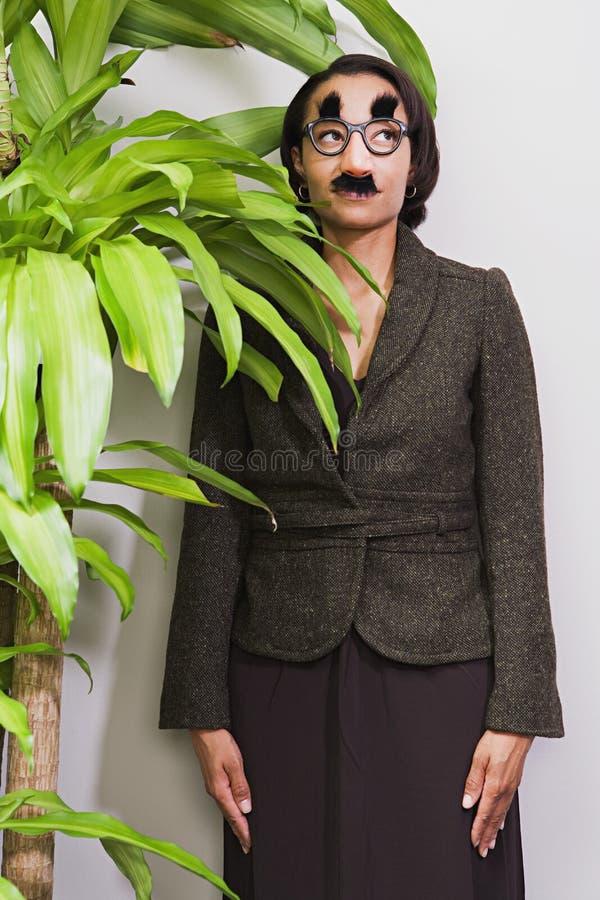 Geschäftsfrau, die hinter Betriebstragender Verkleidung sich versteckt stockbild