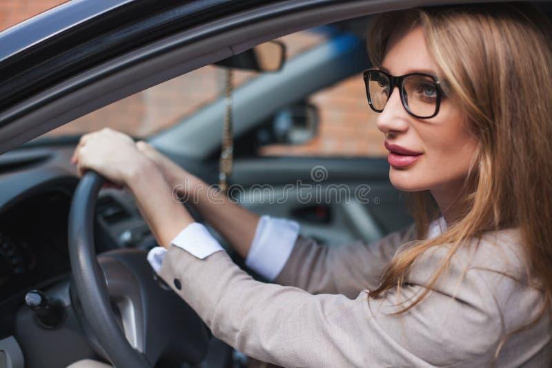 Geschäftsfrau, die in ihrem Auto sitzt Blondine mit dem langen Haar und in den Gläsern lizenzfreie stockbilder
