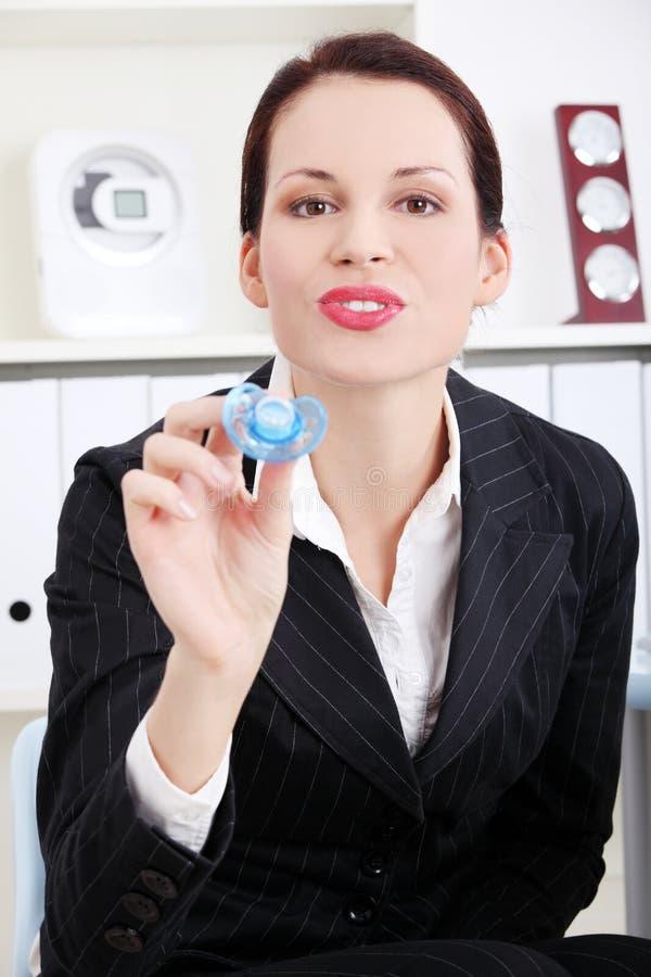 Geschäftsfrau, die ihrem Kind eine Schätzchen `s Attrappe gibt. stockfoto