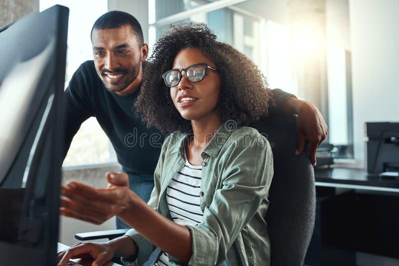 Geschäftsfrau, die ihrem Kollegen auf Computer etwas zeigt lizenzfreies stockfoto