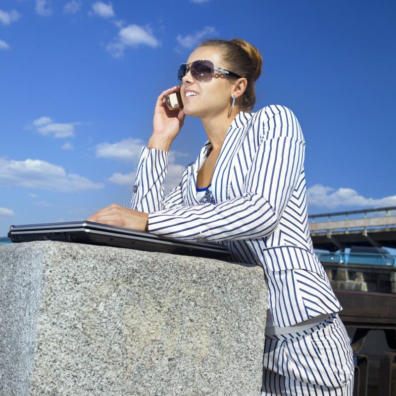 Geschäftsfrau, die ihren Handy verwendet stockfotografie