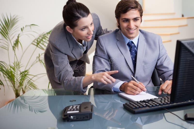 Geschäftsfrau, die ihren Kollegen erklärt, was er tun muss lizenzfreie stockbilder