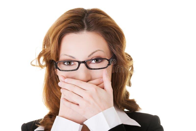 Geschäftsfrau, die ihren Mund wegen der Schande bedeckt lizenzfreie stockfotografie
