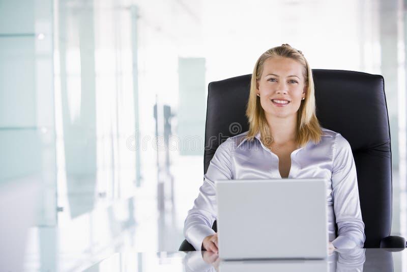 Geschäftsfrau, die im Büro mit Laptop sitzt stockfoto
