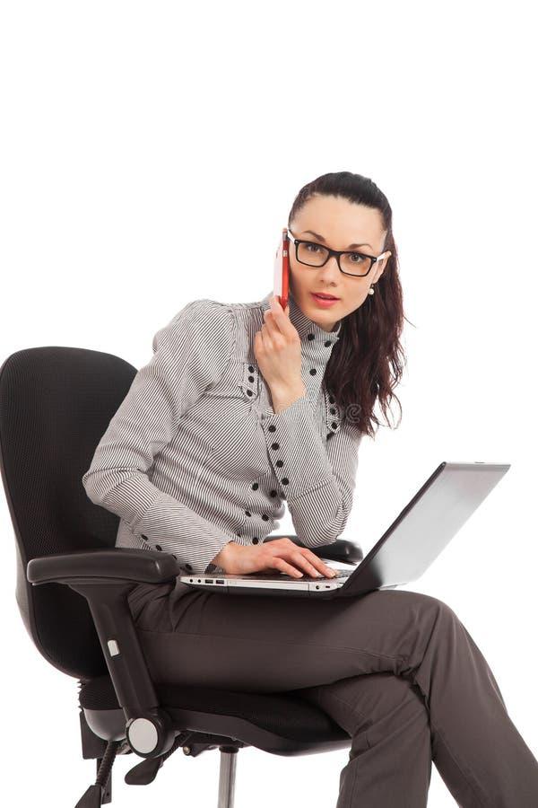 Geschäftsfrau, die im Bürostuhl mit dem Laptop an spricht sitzt lizenzfreies stockfoto