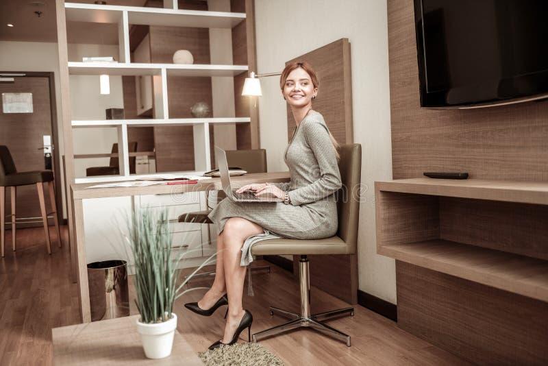 Geschäftsfrau, die im gemütlichen geräumigen Hotelzimmer arbeitet lizenzfreies stockbild