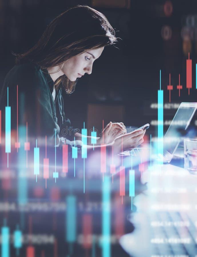 Geschäftsfrau, die im Nachtbüro in der vorderen Laptop-Computer mit Finanzdiagrammen und Statistiken über Monitor arbeitet doppel stockfotografie
