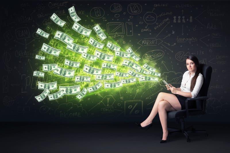 Geschäftsfrau, die im Stuhl hält Tablette mit Dollarscheinen sitzt stockfoto