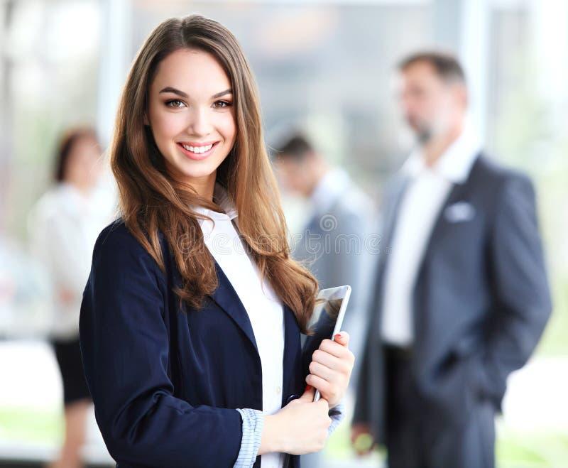 Geschäftsfrau, die im Vordergrund mit einer Tablette in ihren Händen steht stockbilder