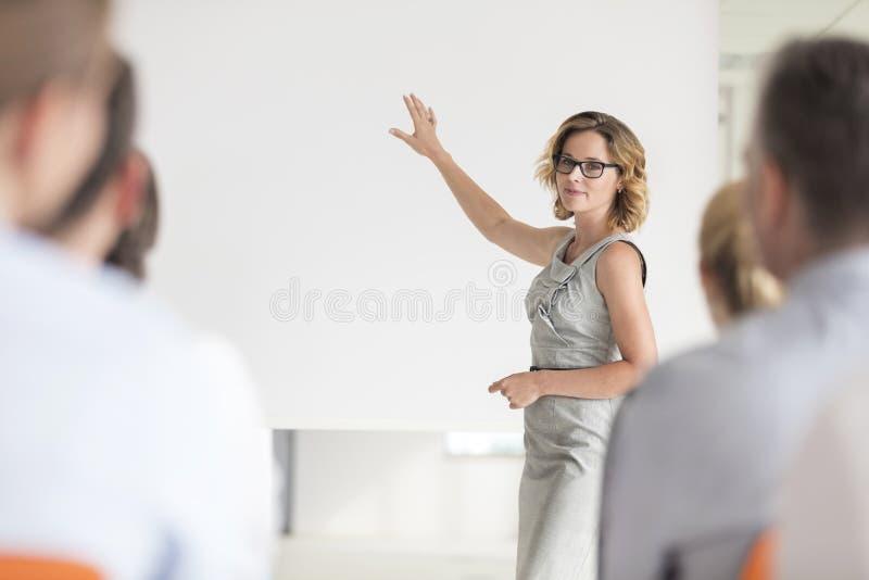 Geschäftsfrau, die Kollegen beim Gestikulieren am Projektorschirm im Büro während des Treffens gedanklich löst lizenzfreie stockfotos