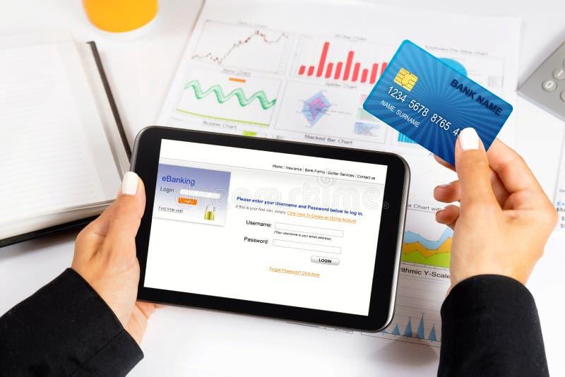 Geschäftsfrau, die Kreditkarte hält und Tablette - e-Bankwesen/online kauft stockbild