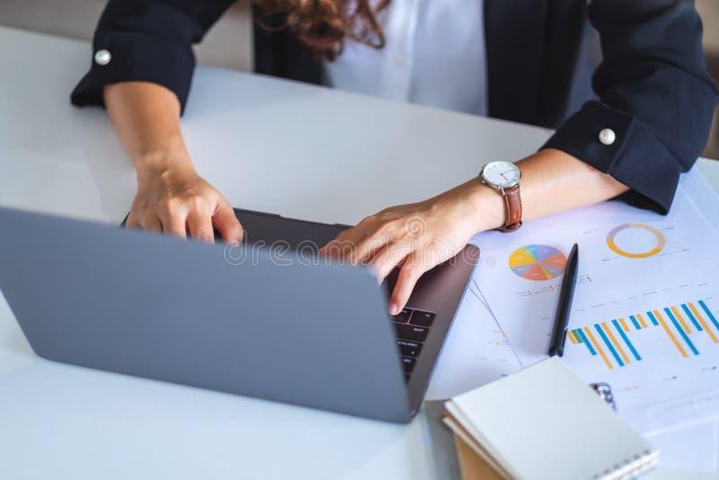 Geschäftsfrau, die Laptop-Computer mit Papierkram auf dem Tisch benutzt und tippt stockfotografie