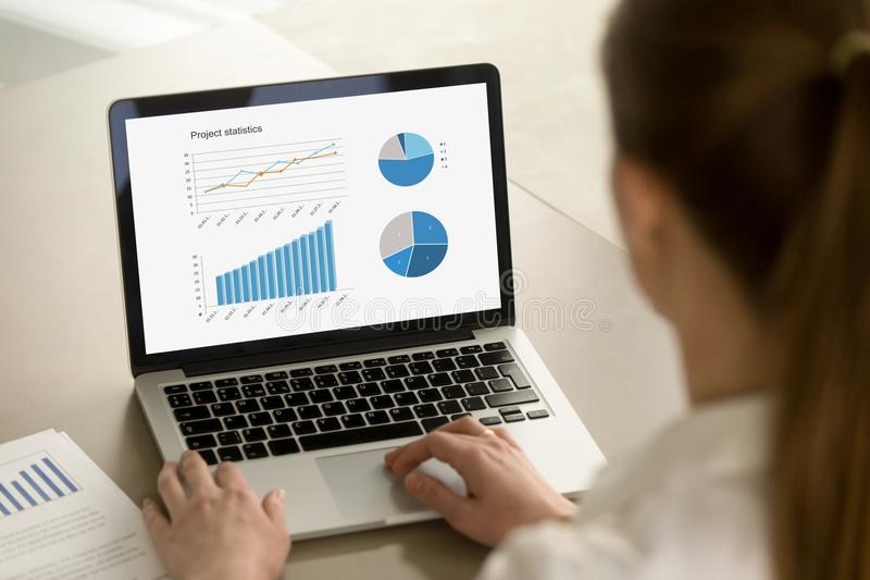 Geschäftsfrau, die an Laptop mit Projektstatistiken über scre arbeitet stockfotos