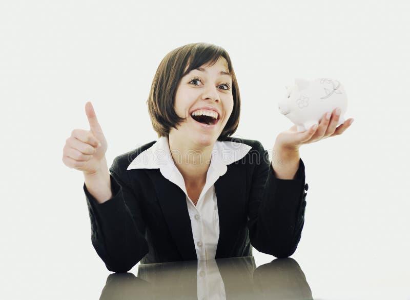 Geschäftsfrau, die Münzengeld in piggy Querneigung einsetzt lizenzfreies stockbild