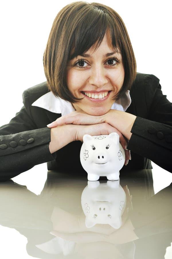 Geschäftsfrau, die Münzengeld in piggy Querneigung einsetzt lizenzfreies stockfoto