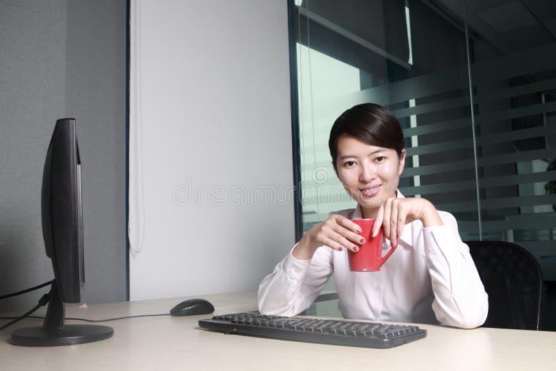 Geschäftsfrau, die mit Computer im Büro arbeitet stockfotografie