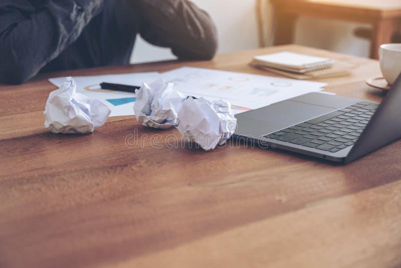 Geschäftsfrau, die mit dem Gefühl wie einem Ausfall und mit geschraubt herauf Papiere und Laptop auf Tabelle im Büro betont arbei lizenzfreie stockfotografie