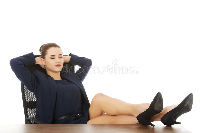 Geschäftsfrau, die mit den Beinen auf Schreibtisch sitzt lizenzfreie stockfotos