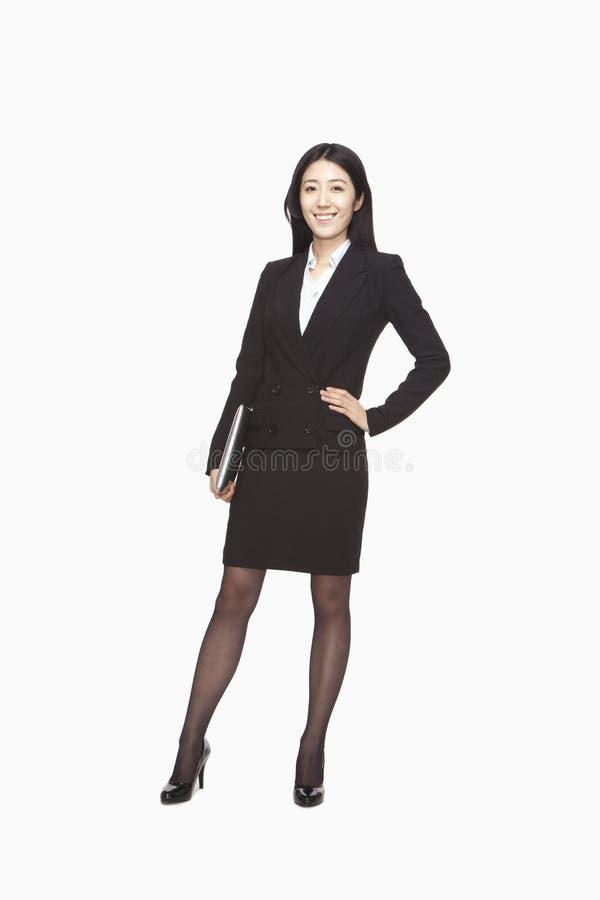 Geschäftsfrau, die mit der Hand auf Hüfte steht stockfotografie