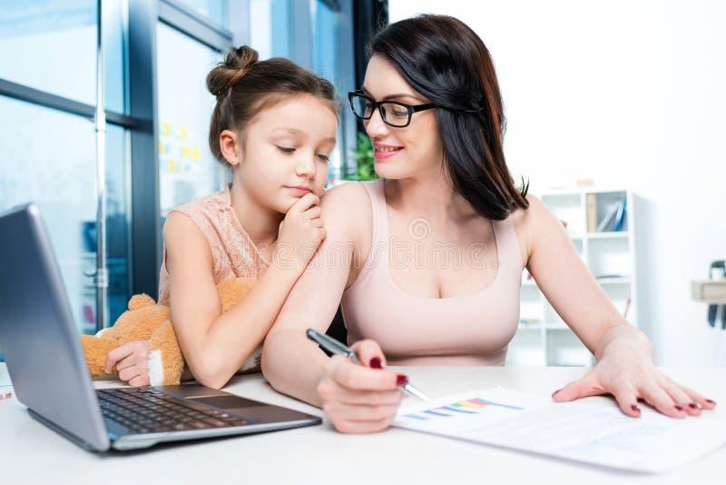 Geschäftsfrau, die mit Dokument und Laptop während Tochter umarmt sie im Büro arbeitet lizenzfreie stockfotografie