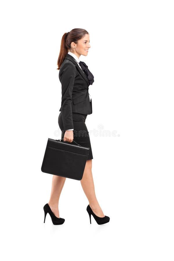 Geschäftsfrau, die mit einem Aktenkoffer in ihrer Hand geht lizenzfreies stockbild