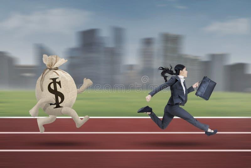 Geschäftsfrau, die mit einer Tasche des Dollars läuft stockbild