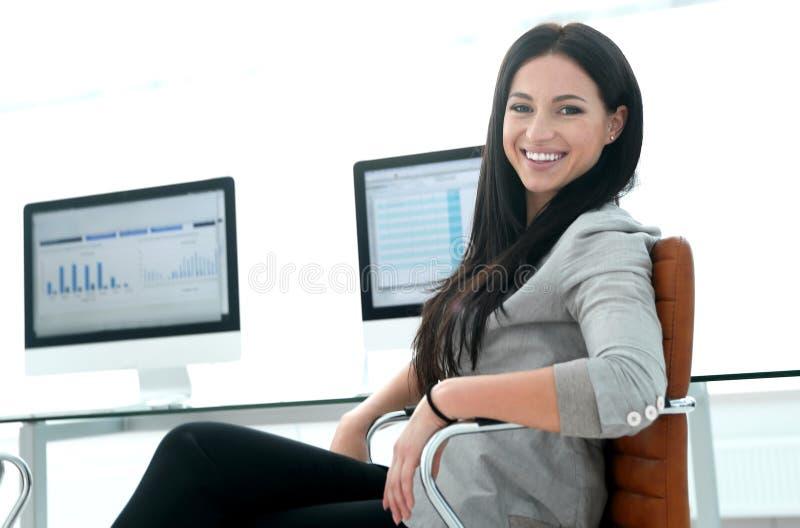 Geschäftsfrau, die mit Finanzdiagrammen auf Computer arbeitet stockbild