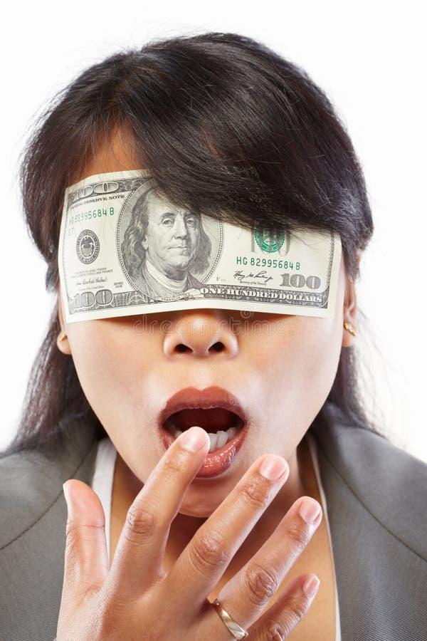 Geschäftsfrau, die mit Geld blind gemacht wird stockfotografie