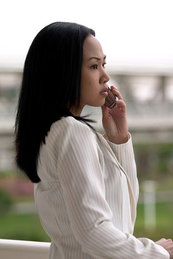 Geschäftsfrau, die mit Handy-Profil schaut lizenzfreies stockbild