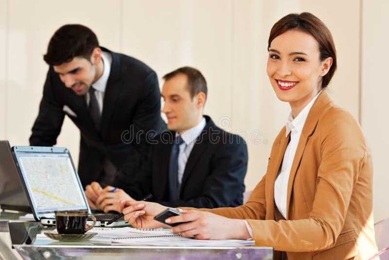 Geschäftsfrau, die mit Kollegen im Hintergrund lächelt stockfoto