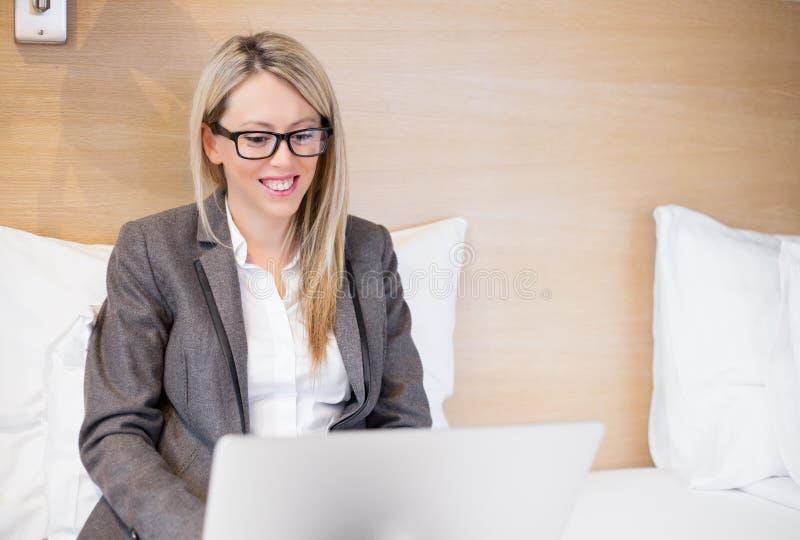 Geschäftsfrau, die mit Laptop-Computer im Bett arbeitet lizenzfreie stockbilder