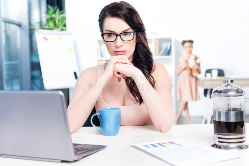 Geschäftsfrau, die mit Laptop im Büro mit Tochter hinten arbeitet stockbild