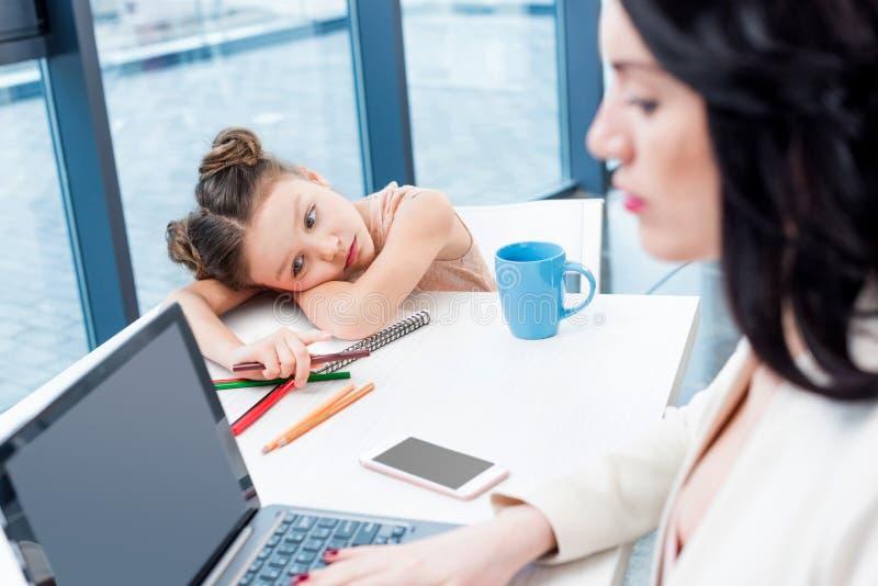 Geschäftsfrau, die mit Laptop während ihre Tochter zeichnet hinten in Büro arbeitet stockbilder