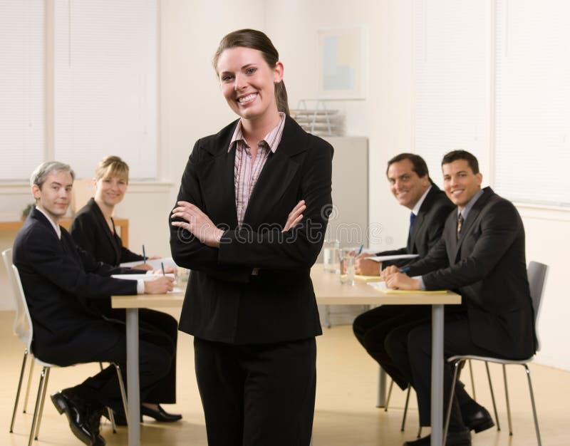 Geschäftsfrau, die mit Mitarbeitern aufwirft lizenzfreies stockbild