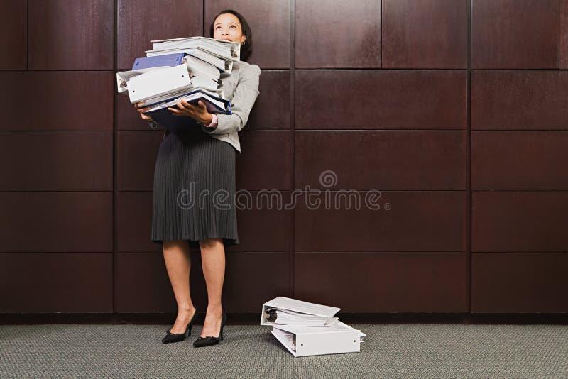 Geschäftsfrau, die mit schweren Dateien kämpft stockfoto