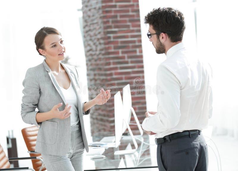 Geschäftsfrau, die mit seinem Assistenten spricht stockfotografie