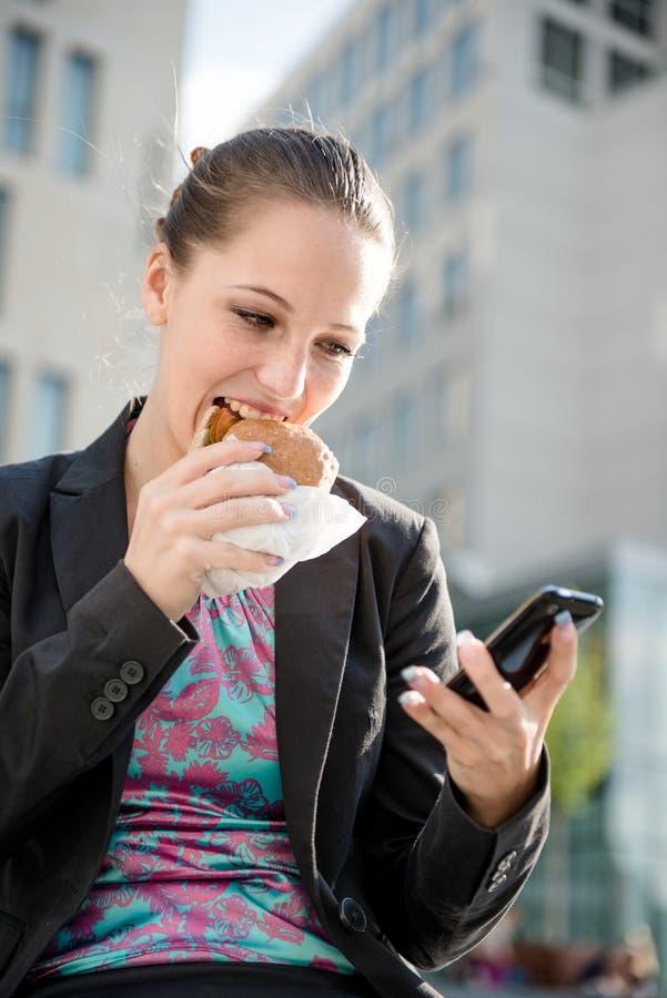 Geschäftsfrau, die mit Telefon isst und arbeitet