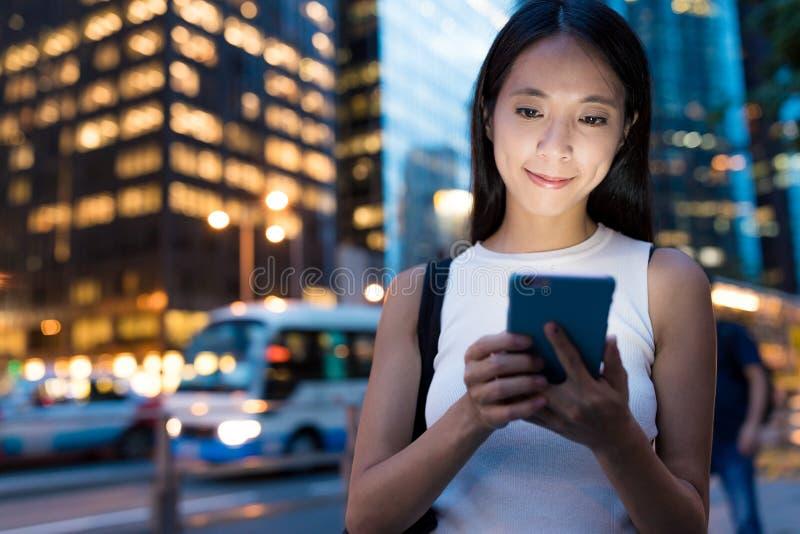 Geschäftsfrau, die Mobiltelefon in der Stadt von Hong Kong verwendet stockbilder