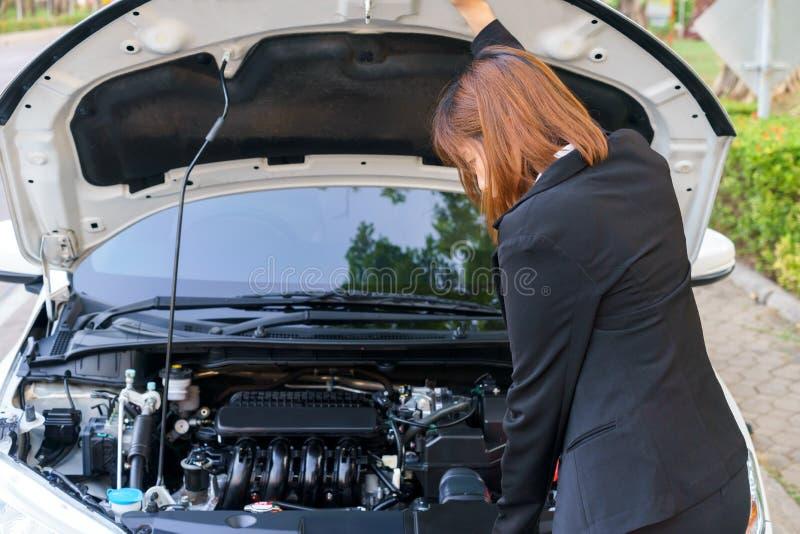 Geschäftsfrau, die Motor mit Autozusammenbruch betrachtet stockbilder
