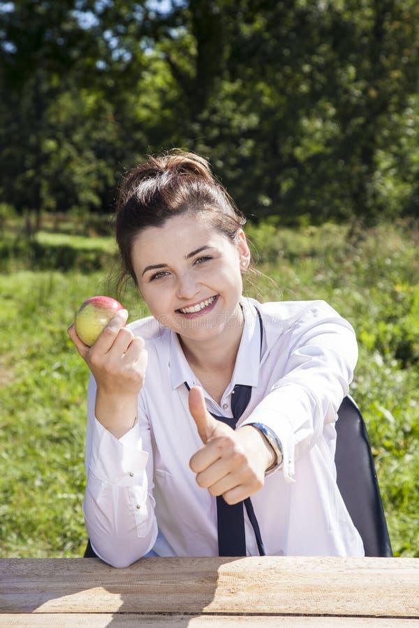 Geschäftsfrau, die oben einen Apfel, Daumen isst lizenzfreie stockfotografie