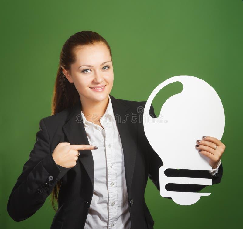 Geschäftsfrau, die Papierbirne auf grünem Hintergrund hält stockfotografie